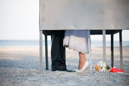 Bride and groom kissing in dressing cabin on the beach