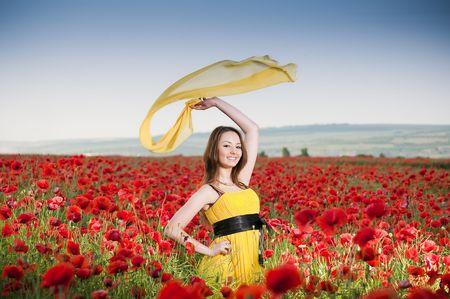 ケシのフィールド内の黄色のドレスの魅力的な女の子 写真素材
