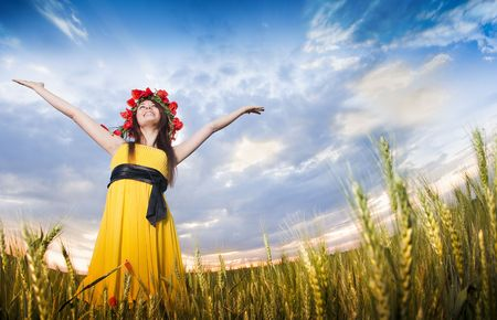 Beautiful young girl in floral wreath in the wheat field, low angle view