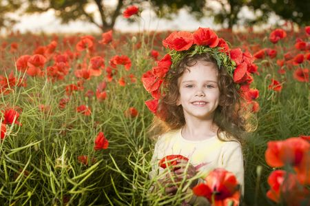 Cute little girl with flowers in the poppy field   photo