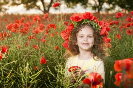 Cute petite fille avec des fleurs dans le champ de coquelicots Banque d'images