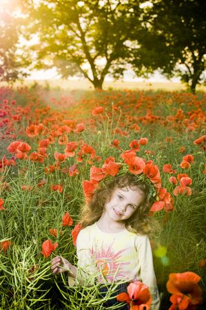 Smiling little girl with flower garland in the poppy field at sunset  photo