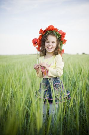 Laughing little girl in floral wreath in the field   photo