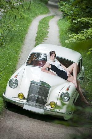 レトロな車の上に座って美しいピンナップ ガール