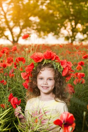 Cute little girl with flower garland in the poppy field at sunset  photo