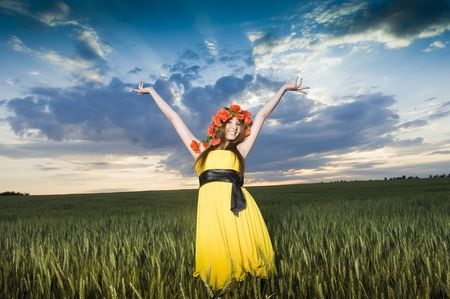Beautiful young girl in floral wreath in the wheat field, low angle view  photo
