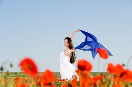 Attractive girl in white dress in the poppy field, low angle view  photo