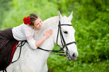 Beautiful girl riding horse in the forest