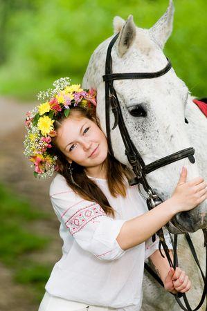 馬と花の花輪で美しい少女
