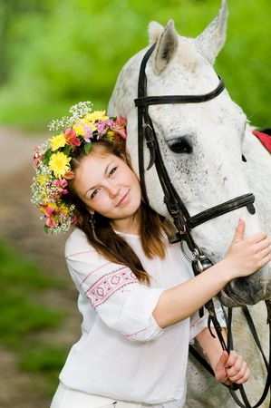 Beautiful girl in floral wreath with horse   Standard-Bild