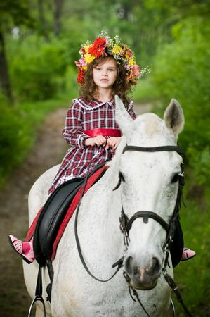 Cute little girl in floral wreath riding horse in the forest  photo