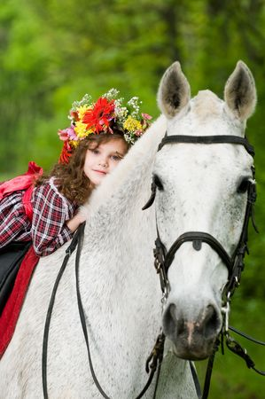 Beautiful little girl in floral wreath riding horse in the forest
