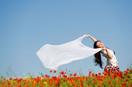 Beautiful girl with white scarf in the poppy field   photo