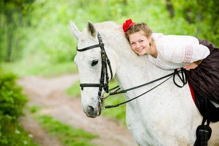 かわいい女の子のフォレスト内の馬に乗って