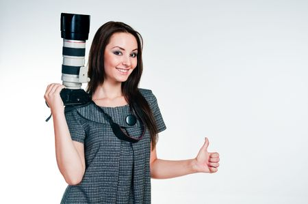 gesticulate: Girl with professional camera giving thumbs up, studio shot