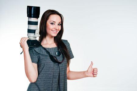Ragazza con telecamere professionali, dando thumbs up, studio shot