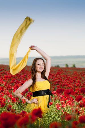 ケシ畑で黄色のドレスの女の子の笑顔 写真素材