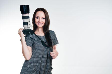 女の子を親指をあきらめることのプロ用カメラに笑みを浮かべて、スタジオ撮影