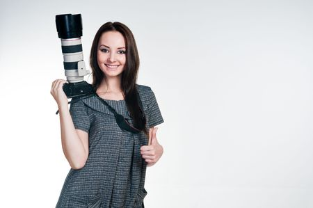 Smiling girl with professional camera giving thumbs up, studio shot  Standard-Bild