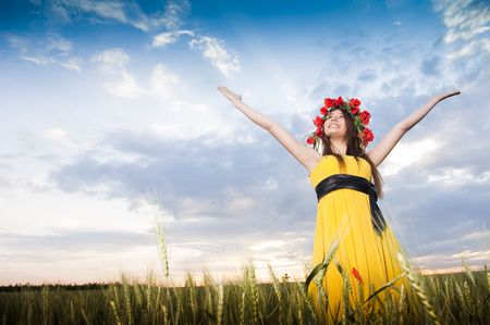 Smiling girl in floral wreath in the wheat field, low angle view  photo