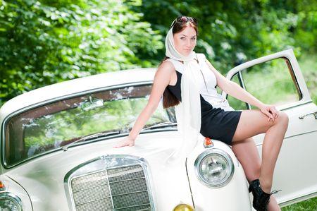 美しいピンナップ スタイル レトロな車に座っている女の子