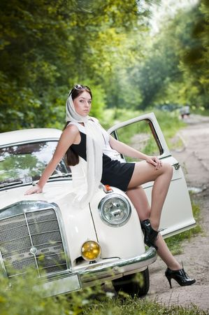 Attractive pin-up styled girl sitting on retro car  photo