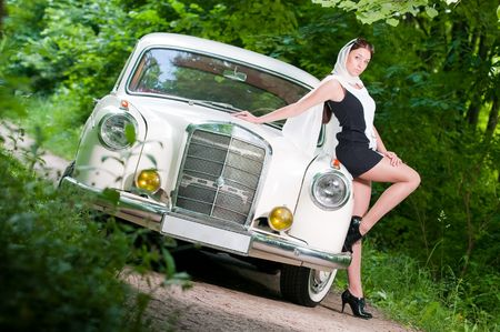 Pin-up styled girl sitting on retro car