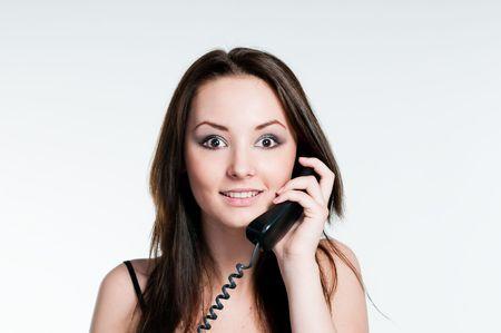 電話、スタジオ ショットに言えば驚く女の子 写真素材