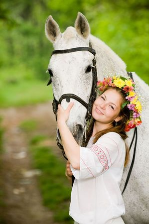 Smiling girl in floral wreath with horse   photo