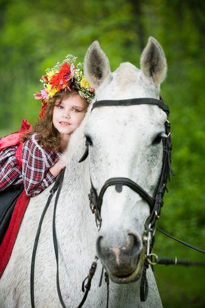 Beautiful little girl in floral wreath riding horse  Standard-Bild