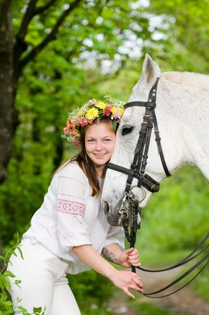 Smiling cute girl with horse in the forest  photo