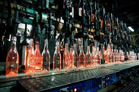 Bottle factory, row of hot transparent glass bottles