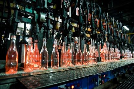 Bottle factory, row of hot transparent glass bottles