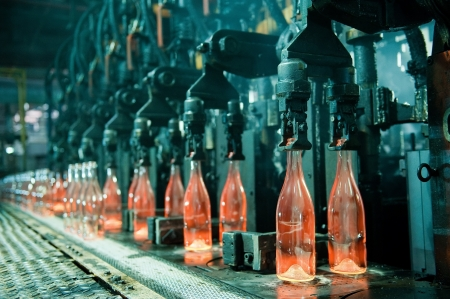 factory line: Row of hot orange glass bottles in factory