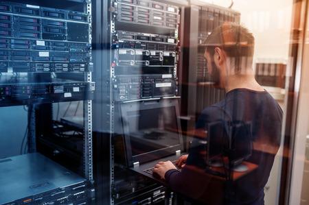 joven hombre de negocios ingeniero con la computadora portátil moderna moderna en la sala de servidores de red Foto de archivo