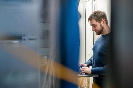 jonge het genereren zakenman met dunne moderne aluminium laptop in netwerk serverruimte