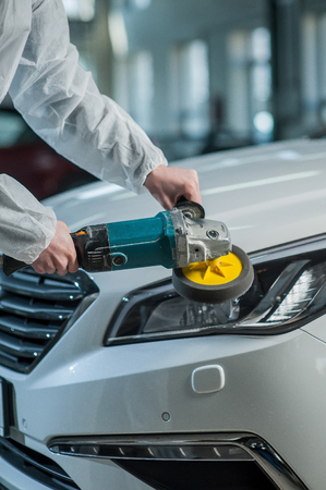 Polished headlights on the car, working car mechanic Stock Photo