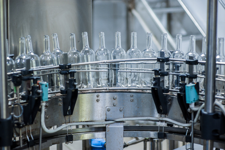 Wine bottles on the machine in production 写真素材