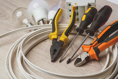 A set of tools electrician, a coil of wire and equipment on a white background