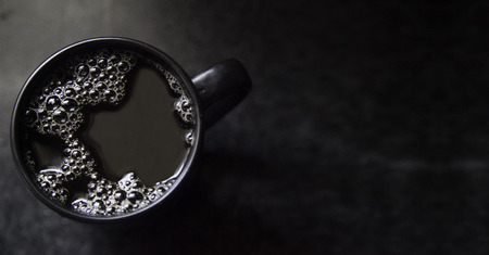 copyspace: Copyspace black, filtered coffee in black cup daylight Stock Photo