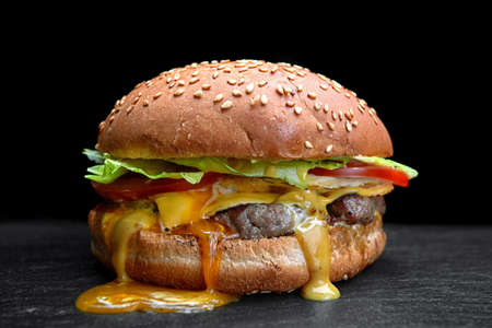 Burger, cheeseburger, hamburger with meat cutlet, cheese, lettuce and tomato, on a black background Standard-Bild
