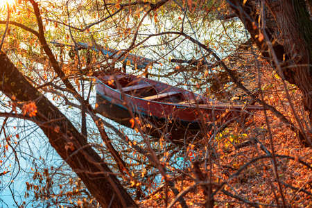 Autumn evening on a deserted river bank with an old fishing bridge and one fishing boat. nobody