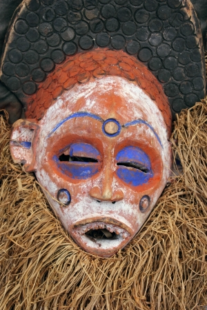 cultural artifacts: Traditional Tribal African Mask with straw beard and blue colored eyes.