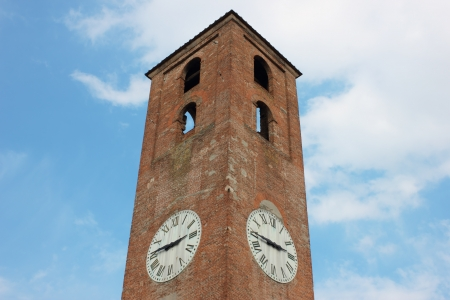 Antique clock tower in Lucca, Italy on blue sky background with white clouds. photo