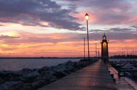 Amazing Sunrise at Desenzano del Garda with the marina and the old Lighthouse.