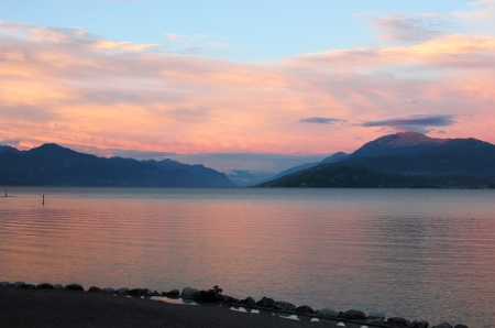 sirmione: Panoramic view of Lake Garda, with colorful sunset over the mountains. Shot near the coast of Sirmione.