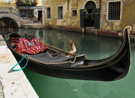 smallest: A beautiful gondola waiting for tourists floating on the water surface of one of the smallest canals in Venice, Italy. Stock Photo