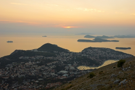 srd: Golden sunset panoramic view of Dubrovnik in Croatia and Dalmatian Coast with a passenger cruise ship leaving the bay. Stock Photo