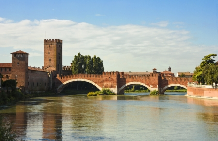 River bank view of the famous The Castelvecchio Bridge in Verona, Italy in a bright sunny day with white clouds in the distance and colorful reflections over the water surface.