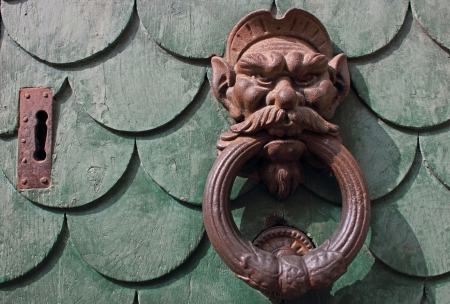 doorknocker: Old green door in Pisa, Italy with am aged rusty handle and key hole.